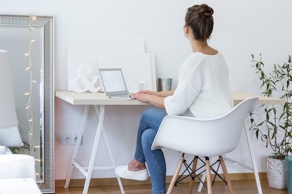 woman working on a laptop in a white room