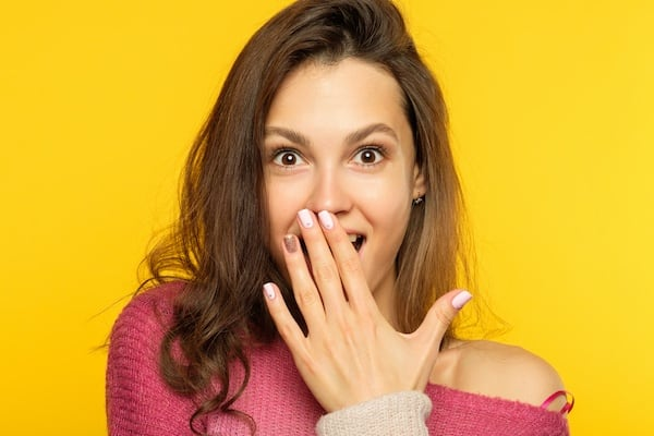 surprised shocked astonished amazed girl covering mouth with hand. unbelievable labor day sale.