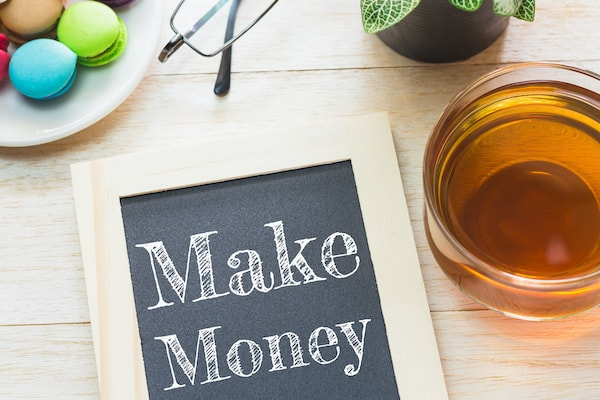 blackboard on a wood table that says make money written with white chalk and a cup of tea on the side