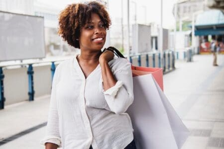 A happy black woman carring shopping bags