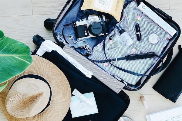 suitcase packed with clothes, a camera, and a hat for a vacation trip.