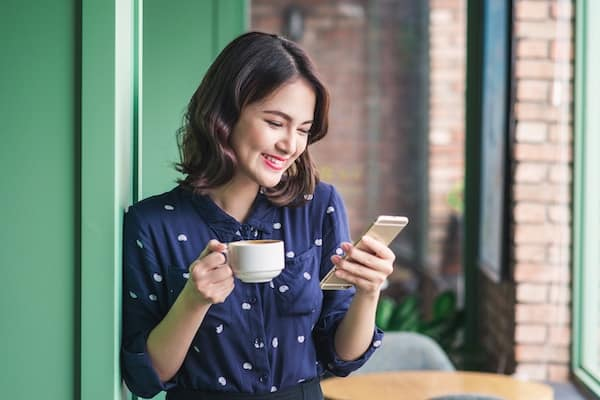 Beautiful cute asian young woman using money making apps on her mobile phone and drinking coffee smiling