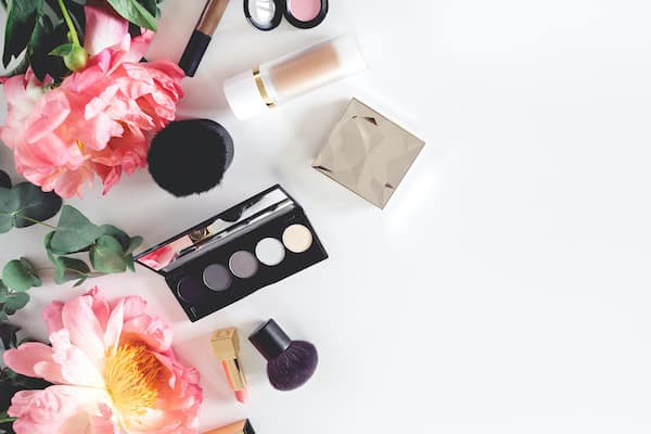 makeup products and pink flowers on a white table