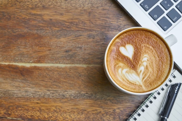 A Laptop, a cup of cappuccino and Notebook with a pen on top of a wood table