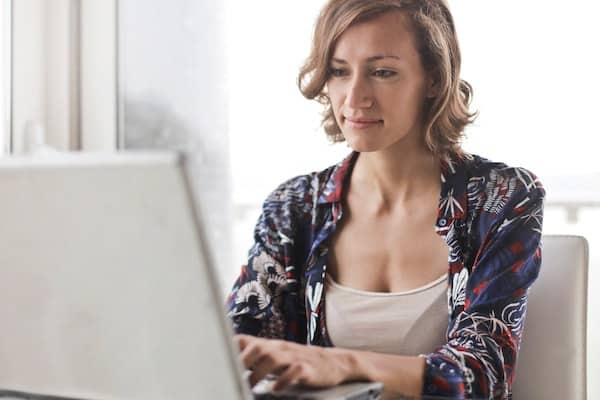 woman in a floral shirt typing on a laptop